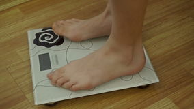 Close up of girl stands on scale for weighing stock video footage
