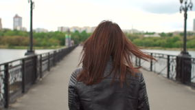 Close-up of girl in sunglasses walking on bridge. Close-up girl takes off sunglasses, turns back and goes over the bridge. Portrait of a beautiful brunette in a stock footage