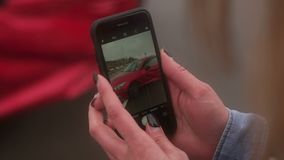 Girl taking pictures on the phone the car that was in an accident on the road.CU. Close-up of the girl taking pictures on the phone the car that was in an stock footage