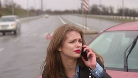 Close-up of the girl talking on the phone after a car accident. Close-up of the girl talking on the phone after a car accident, she was injured and asks for stock footage