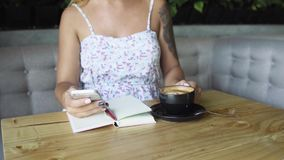 Close-up of girl with tattoo texting on mobile phone and drinking coffee. stock video