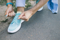 Close-up of girl ties the laces on the shoes while walking aroun Stock Image