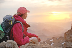 Close-up A girl traveler sits on a rock high in the mountains of the Caucasus against the backdrop of setting sun of Royalty Free Stock Image