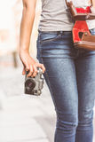 Close up of a girl wearing jean and holding a camera Royalty Free Stock Images
