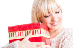 Close-up of girl wearing warm sweater hugging a present Stock Photo