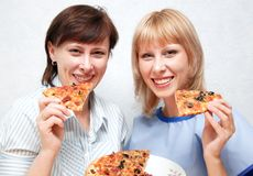 Close-up of girl and woman eating pizza. Women hold in their hands pieces of pizza Royalty Free Stock Photography