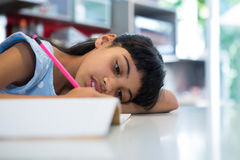 Close-up of girl writing in book. At kitchen counter Stock Images