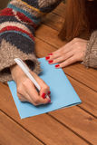 Close-up of girl writing New Year and Christmas congratulation. Close-up of girl writing New Year or Christmas congratulation. Woman with red-coloured nails Royalty Free Stock Photo