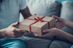 Close up. Girlfriend Giving Gift Box to Boyfriend. Stock Image