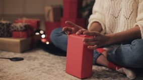 Close up of girls hands preparing presents, finalizing to wrap the present, at cosy home background. Christmas and new. Close up of girls hands preparing stock footage