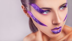 Purple makeup. Close Up of a glamour portrait of beautiful woman model with bright purple makeup royalty free stock photo