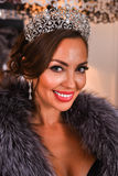 Close-up glamour portrait of smiling  brunette model wearing luxurious tiara and fur coat Stock Images