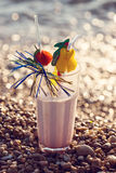 Close up of glass of alcoholic cocktail standing in the sand on a tropical beach Royalty Free Stock Photography