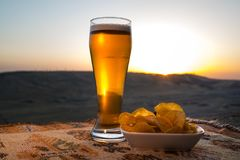 Close Up of A Glass of Beer with the snacks on Sunlight Background, beer on grass Stock Photo