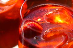 Close up of glass edge of red cocktail with strawberry and  ice cubes royalty free stock image