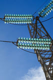 Close-up of glass electrical insulators for high voltage standing out in a blue sky Royalty Free Stock Photo