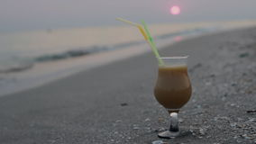 Close up of glass of fruit cocktail on a tropical beach at sunset in the evening. HD stock footage