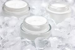 Close-up of glass jar with cream surrounded by ice cubes. Cooling effect skin care product concept. Close-up of glass jar with cream surrounded by ice cubes Royalty Free Stock Photo