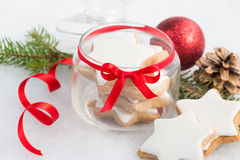 Close up of a glass jar full with christmas homemade star cookies over white fluffy background. Christmas decoration. Stock Photo