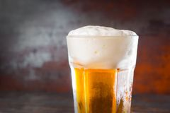 Close up of glass with a light beer and a large head of foam on. Old dark desk. Drink and beverages concept Stock Photos