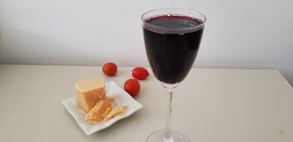 Close up of glass of red vine on white table royalty free stock photo