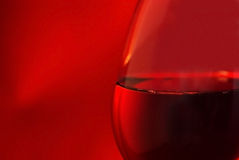 Close up glass of red wine. Close up of a glass of red wine, isolated on red Stock Photos