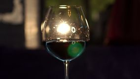 Close-up of a glass of red wine on a blurred dark background. Slow motion. The silhouette of a glass of red wine on the bar against the spotlight stock video footage