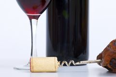 Close up of glass of red wine, bottle and corkscrew Royalty Free Stock Photography