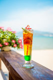Close up of glass with refreshing layered cocktail with lime on beach. Royalty Free Stock Images