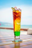 Close up of glass with refreshing layered cocktail with lime on table on beach. Stock Images