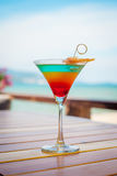 Close up of glass with refreshing layered cocktail with orange and cherry. Royalty Free Stock Photo