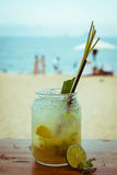 Close up of glass with refreshing lemongrass coctail with mint, lime on sea beach background
