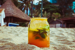 Close up of glass with refreshing orange juice tcocktail with lime and grass on sand of tropical beach Stock Image