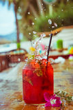 Close up of glass with refreshing strawberry cocktail with lime, mint with splashes on beach bar background Stock Photo