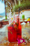 Close up of glass with refreshing strawberry cocktail with lime, mint with splashes on beach bar background Stock Images