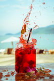 Close up of glass with refreshing strawberry cocktail with lime, mint with splashes on beach bar background Royalty Free Stock Photo