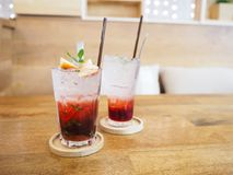 Glass of strawberry juice with soda on wooden table stock image