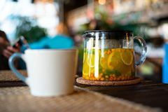 Close-up glass teapot with herbal tea, sea buckthorn and mint on wooden table in restaurant with clay Cup.  stock photo