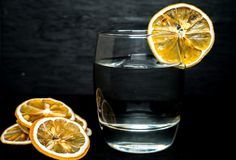Close up glass of water with dried lemon slice in back royalty free stock photo