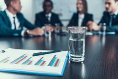 Close up. Glass with water and image of charts lie on table, behind which business meeting is held. Stock Photo