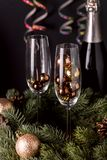 Close Up Glasses with Decoration and Champagne Bottle Wooden Background Christmas New Year Holidays Card New Year Background Verti. Cal Toned Fir royalty free stock photo