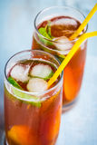 Close up of glasses with homemade ice tea, peach flavored. Freshly cut peach slices for arrangement. Top view. Royalty Free Stock Image