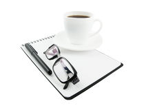 Close-up of glasses, note pad, pen, cup Royalty Free Stock Photo