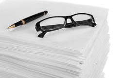 Close up of glasses and pen on a stack of paper. Stock Photos