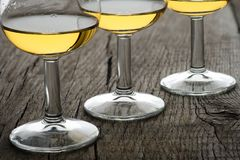 Close-up glasses with single malt whisky in back lit. On rustic wooden board stock photography