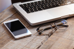 Close up of glasses, smartphone and laptop on a wooden desktop. Royalty Free Stock Images