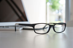 Close up glasses on work desk with laptop Royalty Free Stock Photography