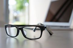 Close up glasses on work desk with laptop Stock Photo