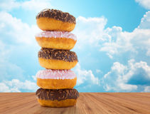 Close up of glazed donuts pile over blue sky Stock Image