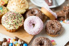Close up of glazed donuts and sweets on table Royalty Free Stock Photos